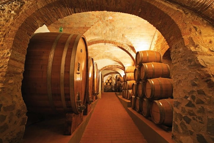 Large and small wine barrels in underground wine cellar