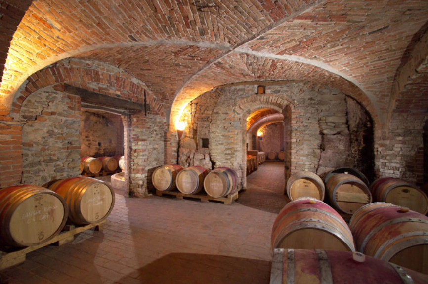 Stone arched wine cellar with wine barrels