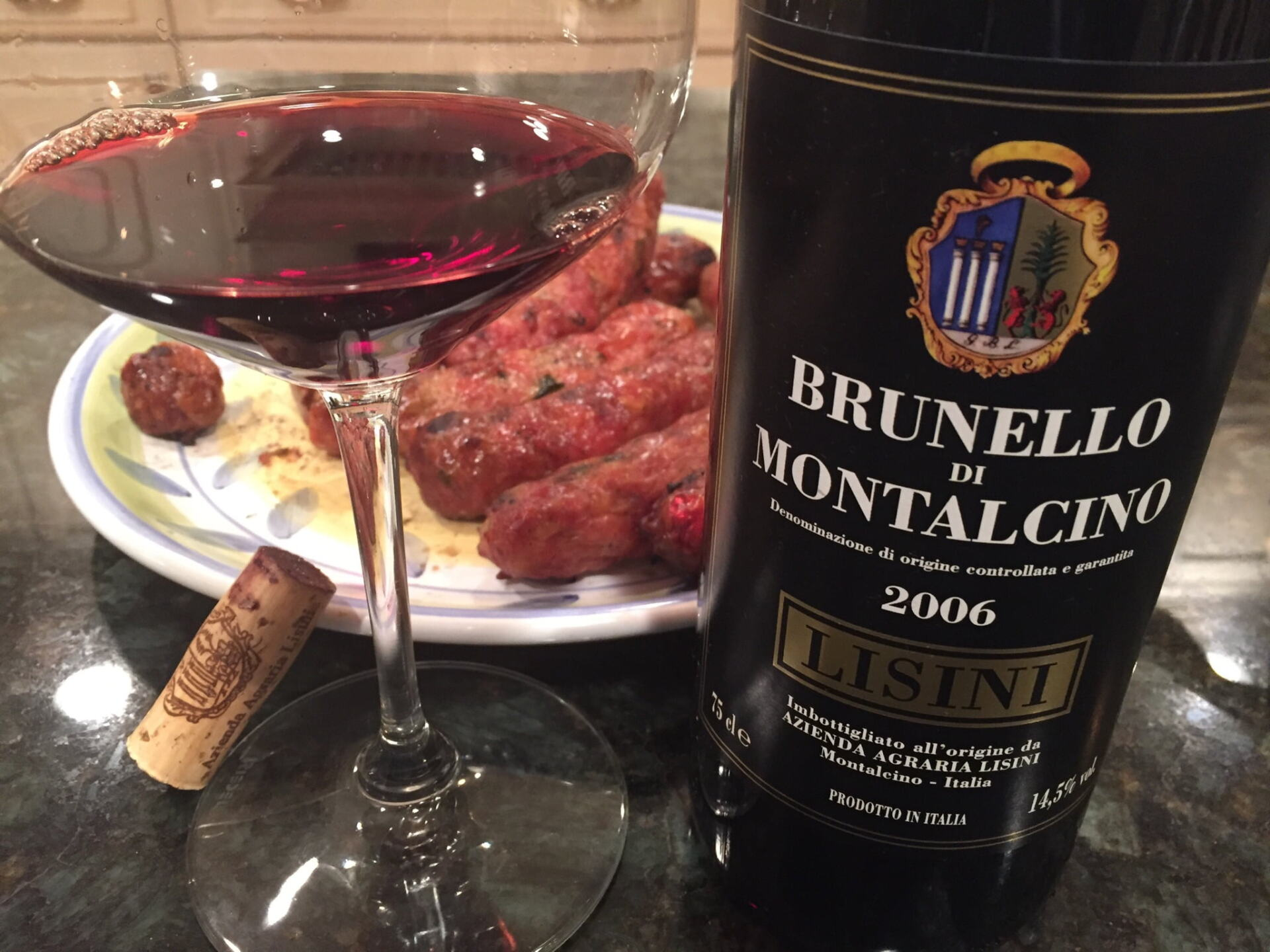 Brunello bottle with glass of red wine and grilled sausage