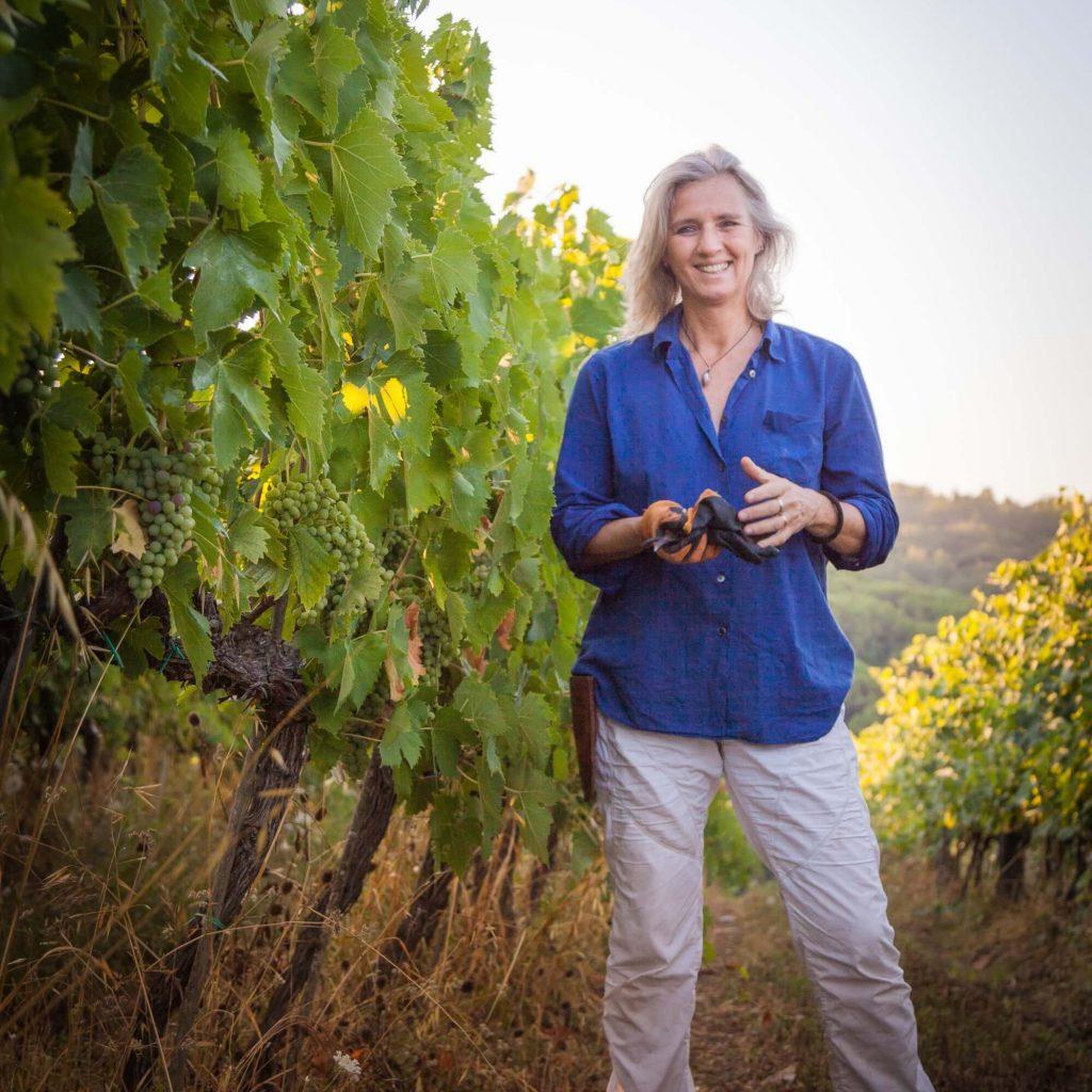 Woman standing among Pomona grape vines