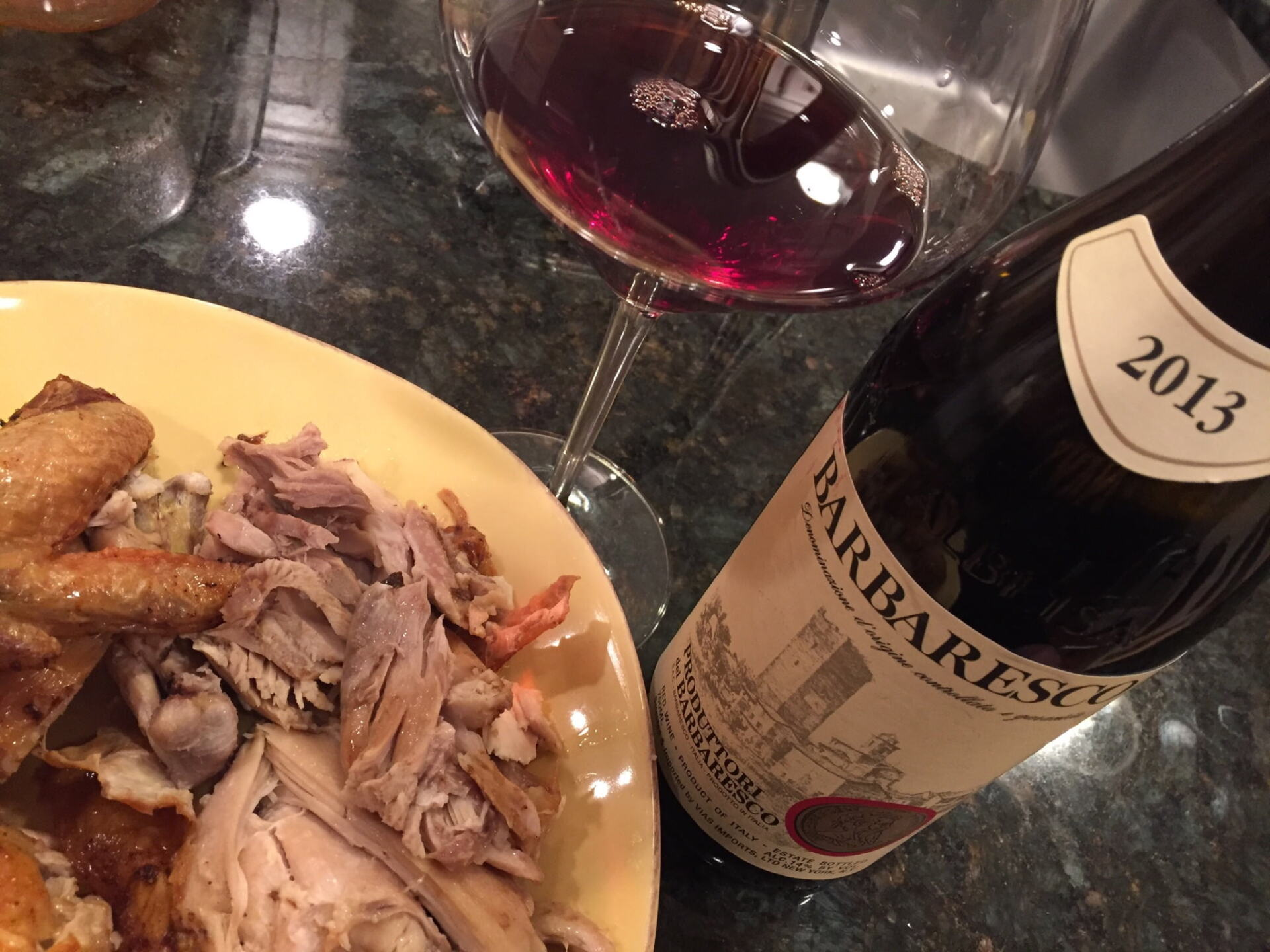Roasted chicken, Barbaresco wine bottle and red wine in glass