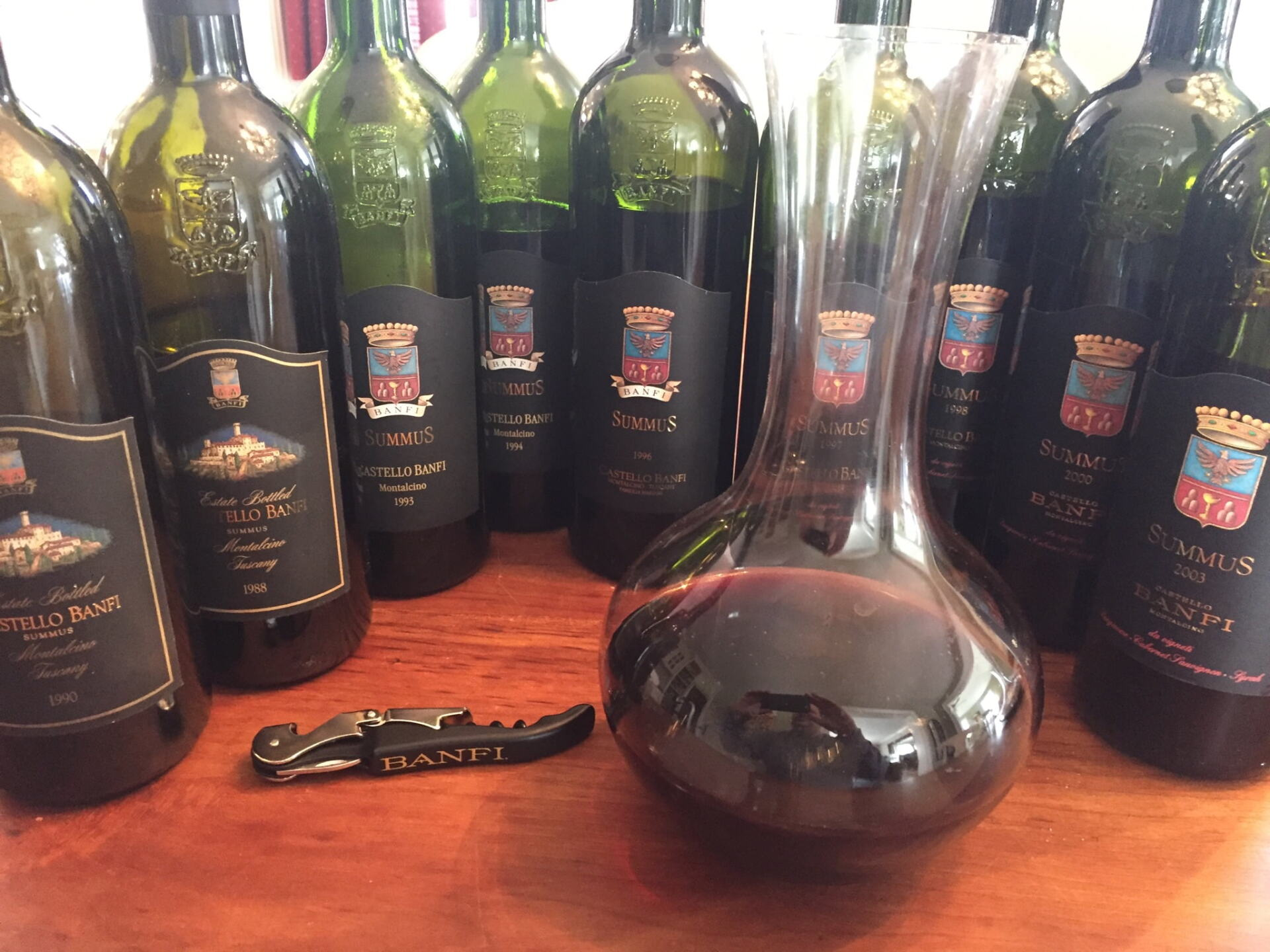 Corkscrew, decanter filled with red wine and 9 wine bottles of Summus