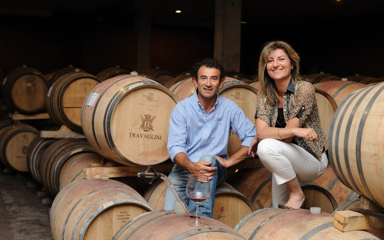 Man and woman on barrels in wine cellar